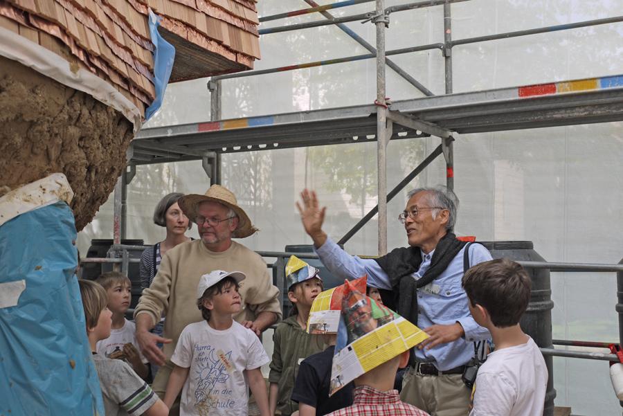 Der Künstler, die Kinder und der Claytec-Mann (mit Strohhut)