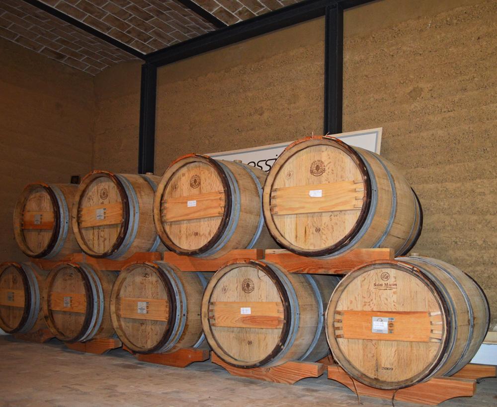 """Barrique-Fässer im """"simulierten Kellerraum"""" - im Hintergrund die Stampflehmwand aus CLAYTEC-Lehm"""